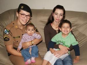 Ao lado da mãe, Soldado Edivane segura no colo bebê que ajudou a salvar. Crédito da foto: Francine Herpich