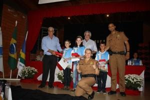 Os alunos Willian, Isadora e Vinicius receberam brindes pelas redações sobre o Proerd. Foto de divulgação
