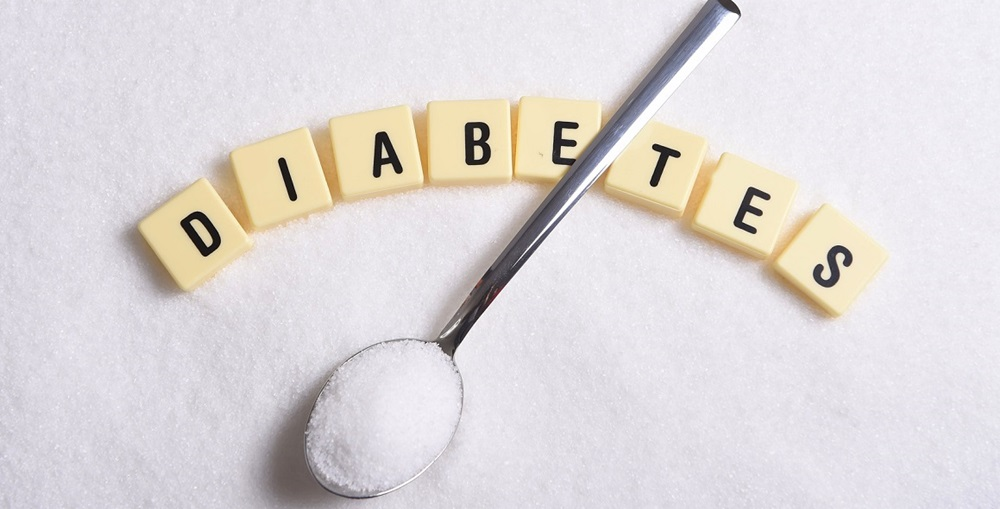 diabetes block letters in crossword and spoon over sugar pile