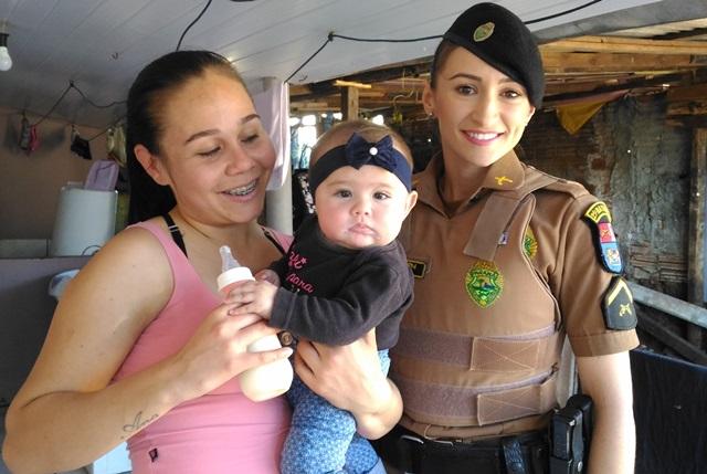 Laísa, agora bem, no colo da mãe Ana Paula junto da soldado Sandra Schons durante visita nesta terça-feira (25). Foto: Evandro Artuzi/RBJ